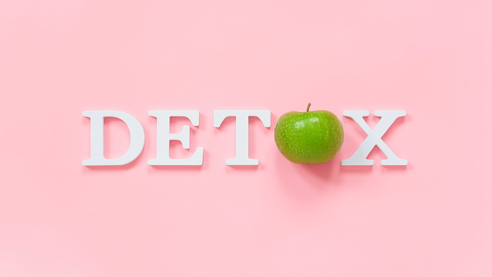 Body detoxification and healthy diet concept. Green natural fresh apple in word DETOX from white letters on pink background. Creative flat lay Top view Copy space.